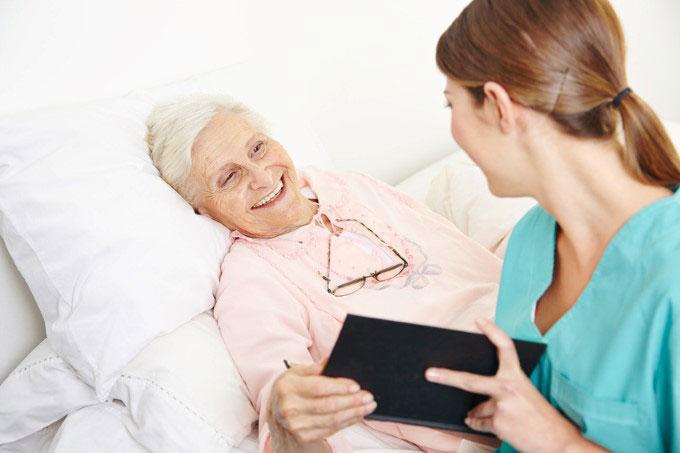 Pflegerin lacht mit Patientin