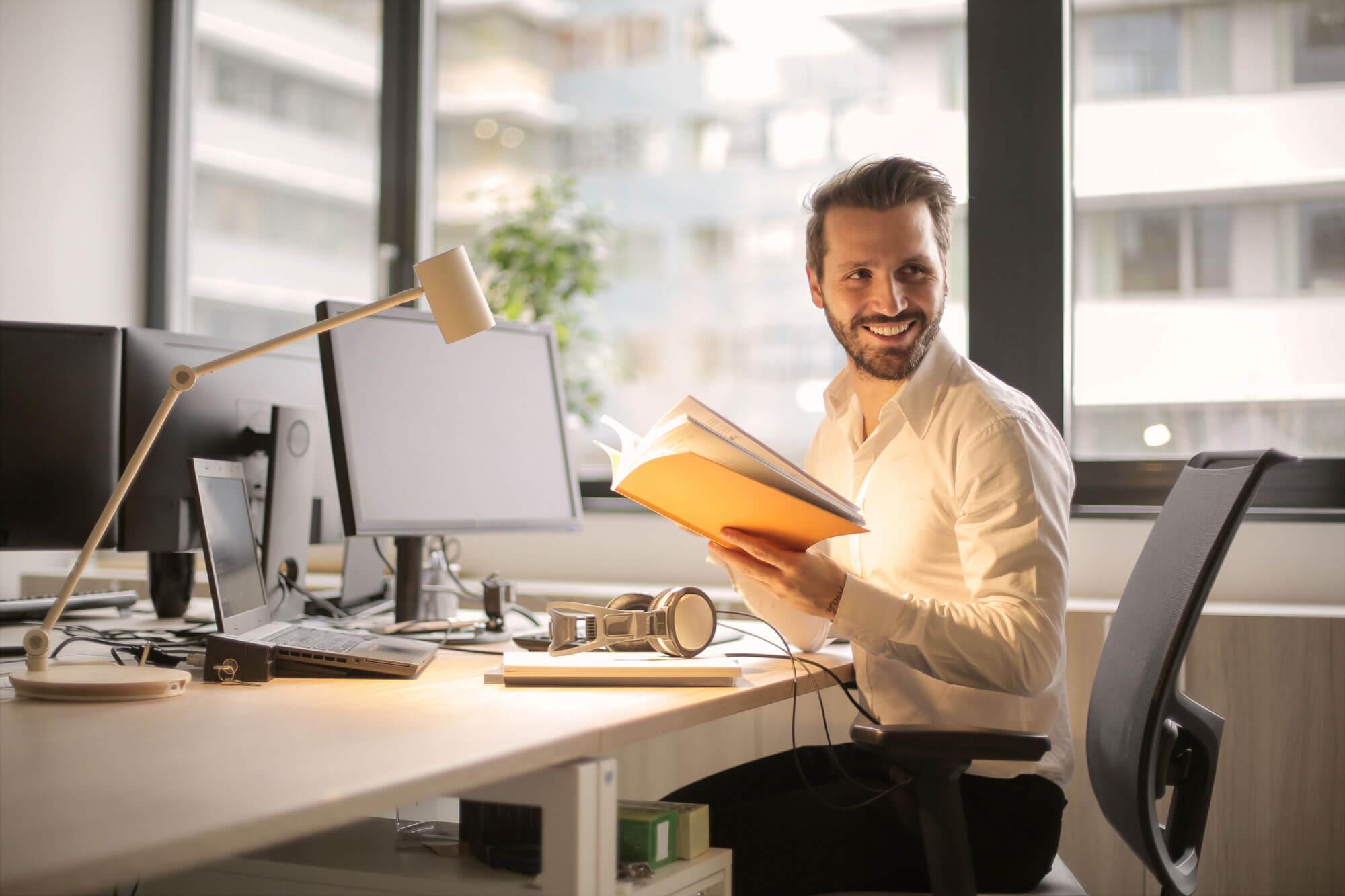 Mann im Büro hält Buch in der Hand